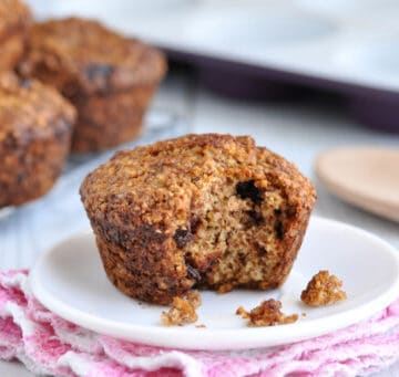 Healthy Oat Bran Muffin with Chocolate Chips with a bite taken out on a white plate