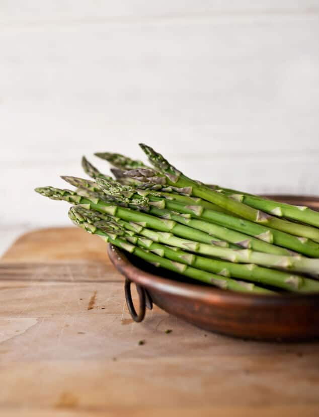 A brown bowl filled with asparagus