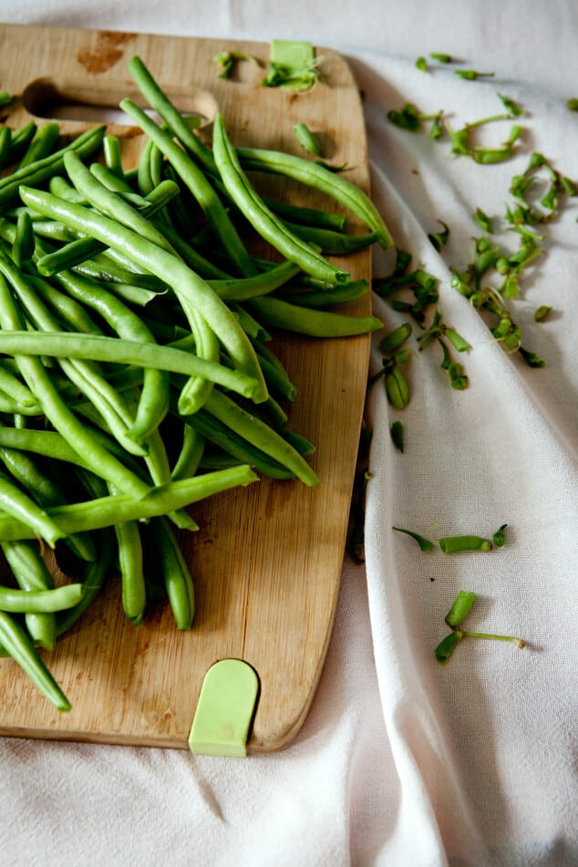 A chopping board covered in sliced green beans