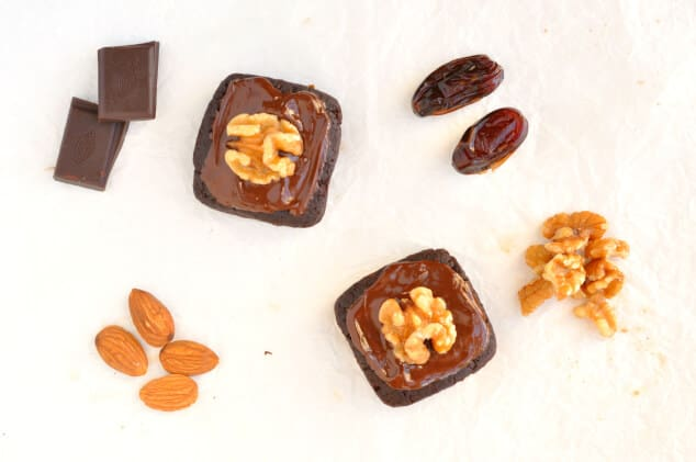 Overhead shot of raw vegan brownies topped with melted chocolate and walnuts