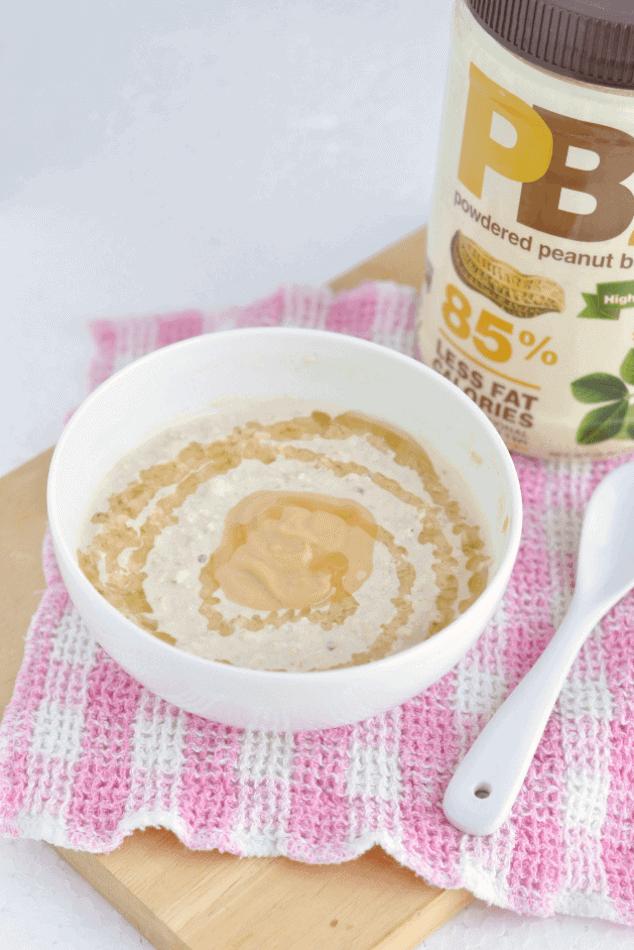 A bowl of peanut butter overnight oats next to a jar of PB2.