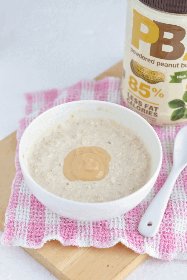 A bowl of peanut butter overnight oats topped with a spoonful of peanut butter.