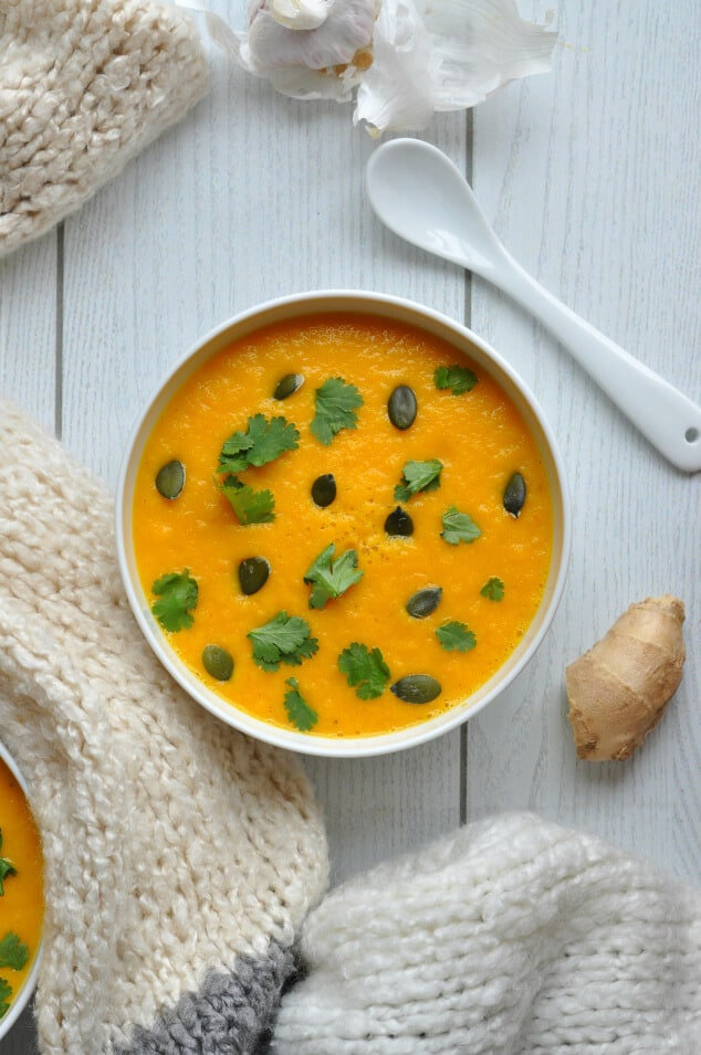An overhead shot of a single bowl of creamy carrot and coriander soup.