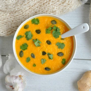 An overhead shot of creamy carrot and coriander soup in a bowl.