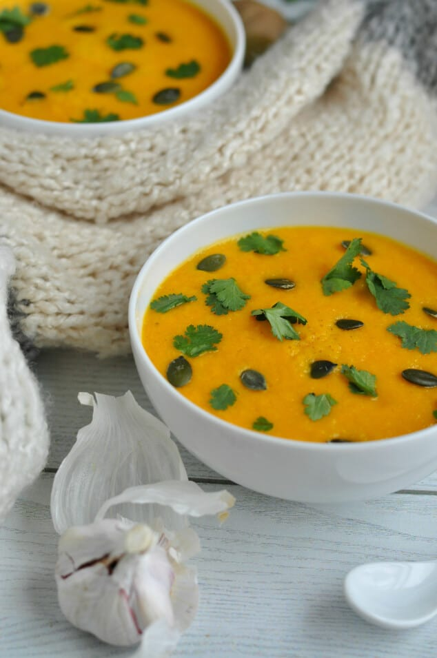 Two bowls of creamy carrot and coriander soup next to a garlic clove.
