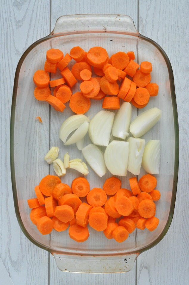 Raw carrots and onions in a roasting tray.