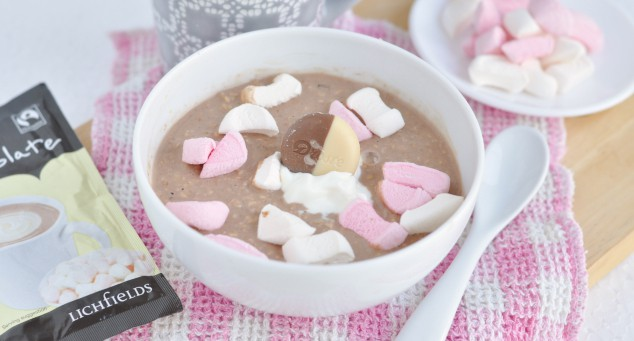 A bowl of hot chocolate overnight oats topped with marshmallow pieces next to a spoon.