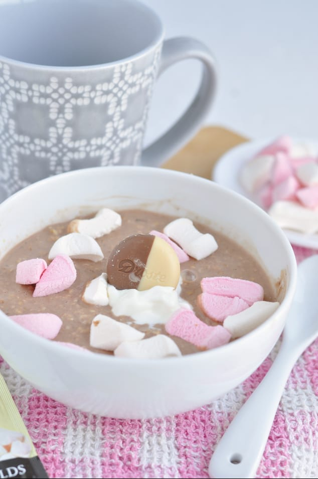 A bowl of hot chocolate overnight oats covered in marshmallow pieces with a big chocolate coin in the centre.