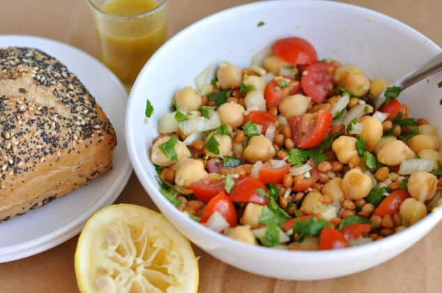A bowl filled with lentil chickpea salad next to a bread roll.