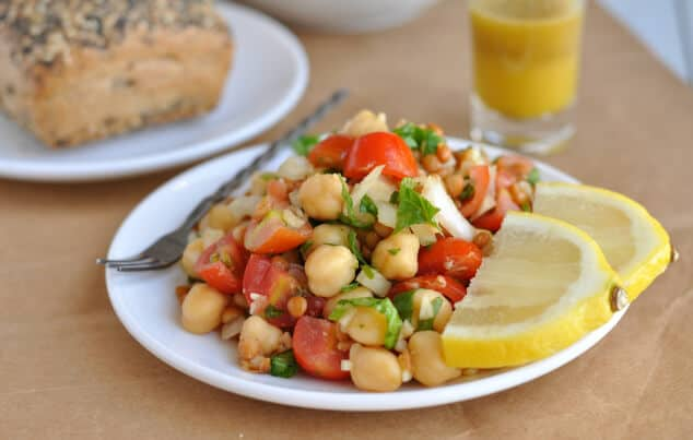 A plate full of lentil chickpea salad with two lemon slices and a shot glass of dressing.