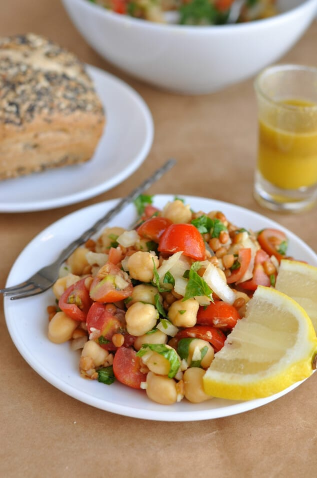 A plate of lentil chickpea salad with lemon slices next to a bread roll.