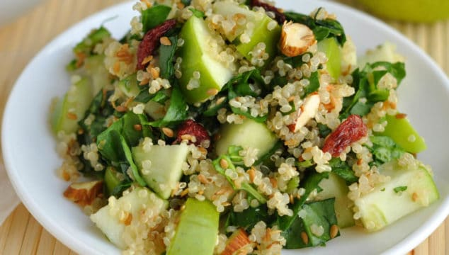 A small white salad plate piled high with a serving of quinoa spinach salad.