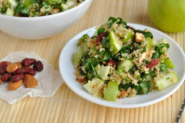 A plate of spinach quinoa salad next to some dried cranberries and almonds.