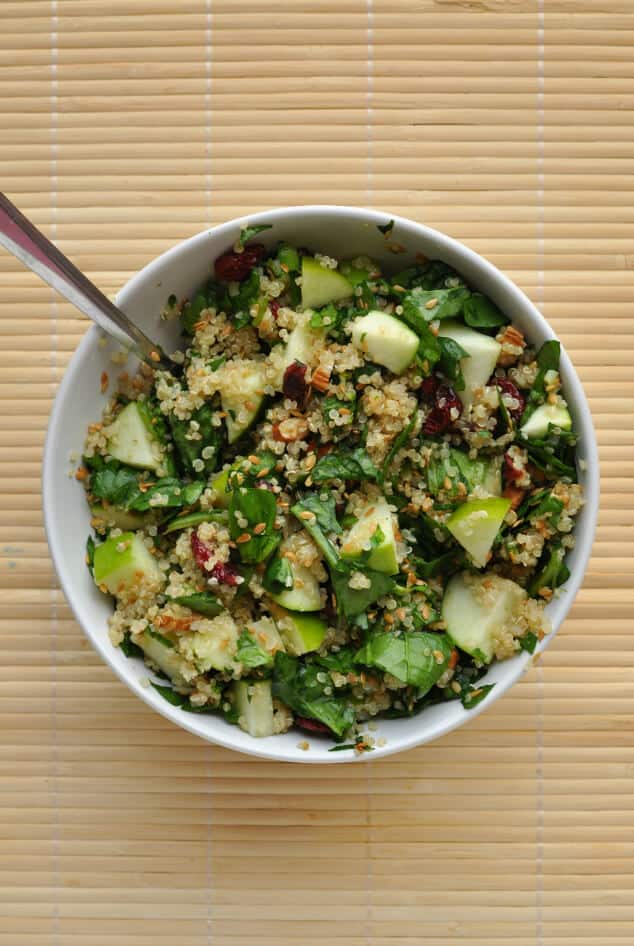 A mixing bowl filled with all the ingredients needed for a spinach quinoa salad.