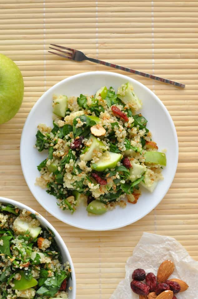 An overhead shot of a plate of spinach quinoa salad next to a fork.