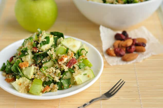A small white plate topped with spinach quinoa salad.